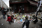 People laying flowers and candles in front of one of the establishments targeted terror attacks in Paris