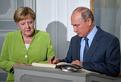 Russia's President Vladimir Putin signs a distinguished visitors' book as he meets with German Chancellor Angela Merkel