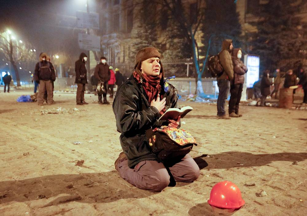 A protester prays as he holds an open Bible during an anti-government protest in downtown Kiev