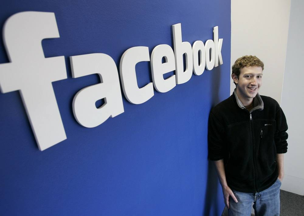 Facebook founder Mark Zuckerberg posing at one of the world's best known brand logos