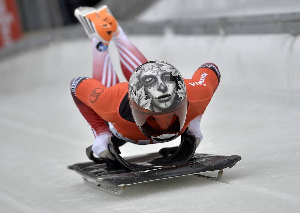 Sarah Reid from Canada jumps on her sledge during the women's Skeleton World Cup in Germany. The skull painting on her helmet symbolises the danger of the sport she practises