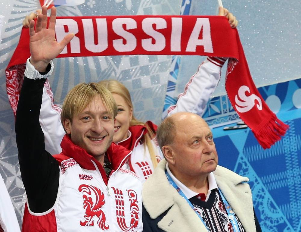 Russian figure skater Evgeni Plushenko and his coach Alexei Mishin (left to right) during the figure skating team competition in Sochi