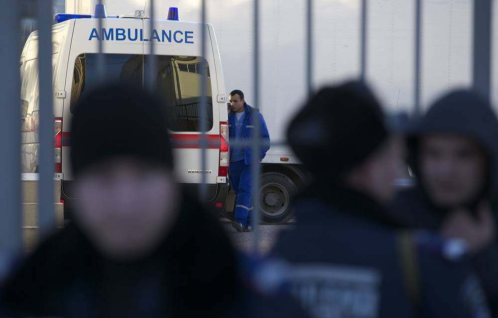 An emergency worker walks next to an ambulance at a territory close to an Ukrainian military unit in Simferopol