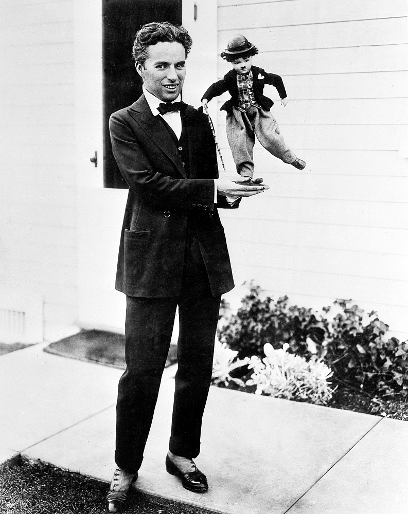 """Charlie Chaplin holding a doll of  """"the Tramp"""", 1917"""