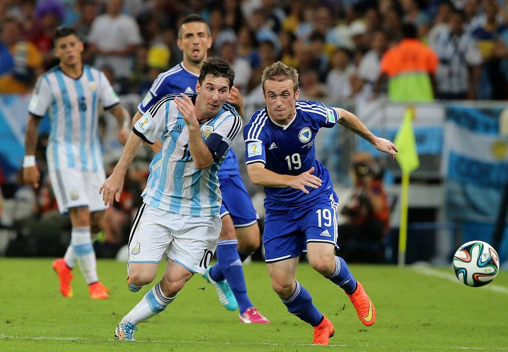 Lionel Messi (L) of Argentina in action with Edin Visca (R) of Bosnia and Herzegovina