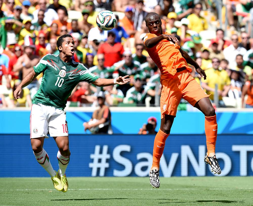 Giovani Dos Santos (L) of Mexico and Bruno Martins Indi of the Netherlands