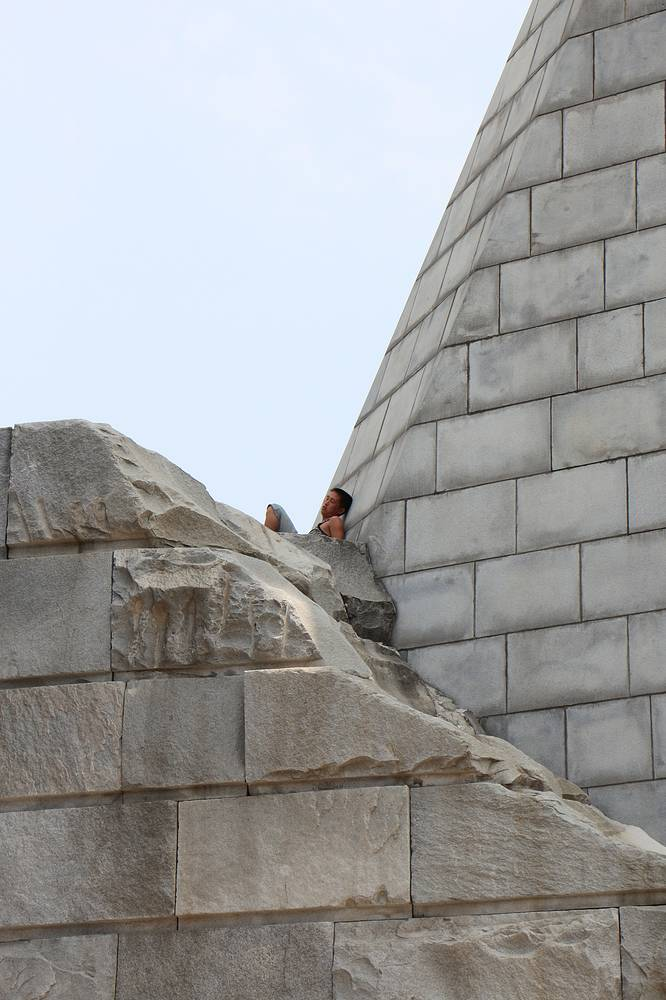 A local rests on the monument to Workers' Party of Korea