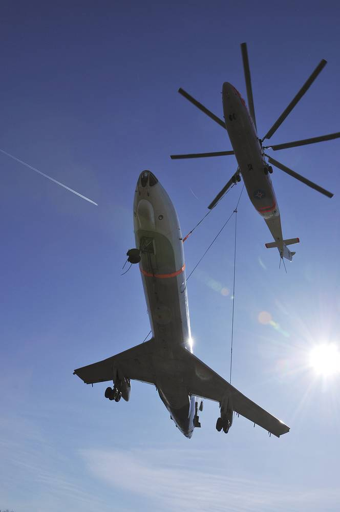 Mi-26 helicopter transports a plane