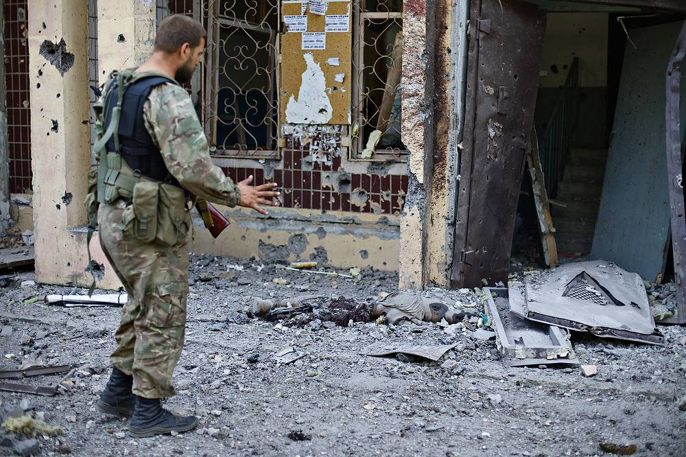 A militia fighter seen near a destroyed house in Donetsk