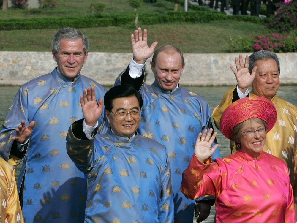 Then US President George W. Bush, China's Hu Jintao, Russian President Vladimir Putin, Chile's Michelle Bachelet and Thailand's then Prime Minister Surayud Chulanot wearing Vietnamese national costumes