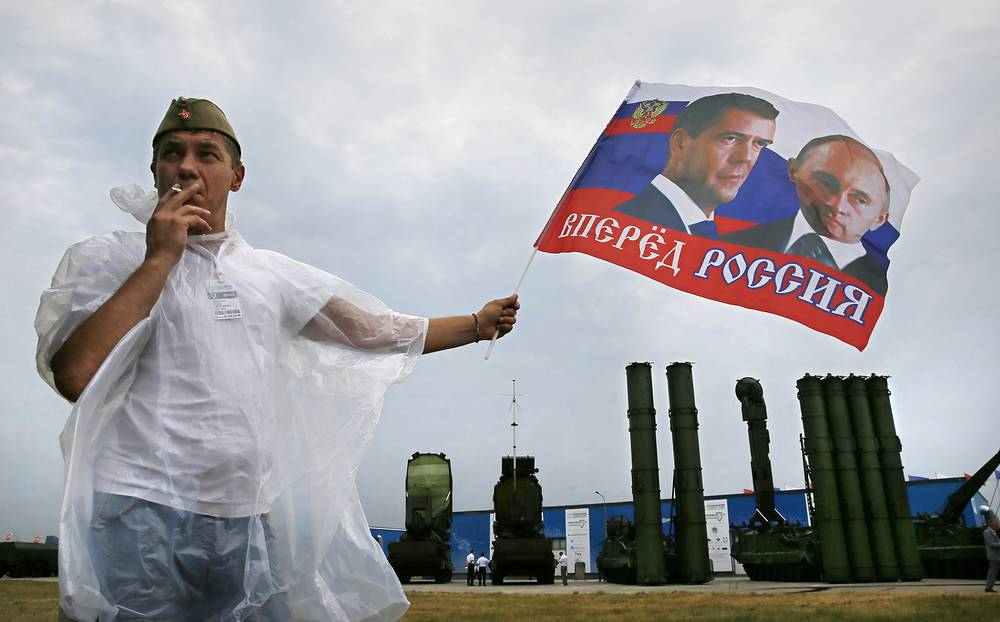 A man holds a flag with the portrait of Russian President Vladimir Putin and Russian Prime Minister Dmitry Medvedev in front of a Russian air defense system S-300