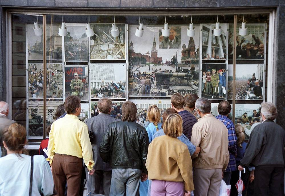 People gather to see images of the state coup attempt in 1991