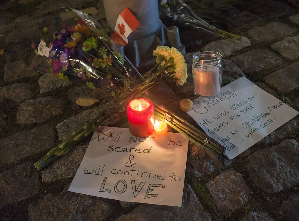 Photo: A makeshift memorial sits on a downtown street one block away from Canada's National War Memorial in Ottawa, Canada, 22 October 2014