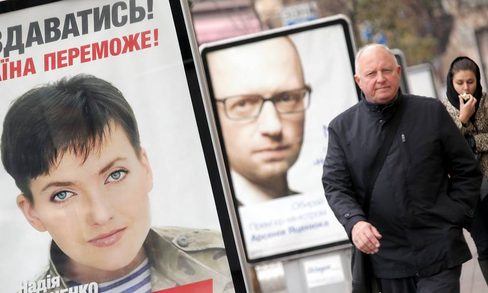 Acting Prime Minister Arseniy Yatsenyuk tops the list of People's Front party. Yulia Tymoshenko's party Batkyvshchina put Nadezhda Savchenko who is currently on trial in Russia first in its list of candidates. Photo: Pre-election posters with portraits of Nadezhda Savchenko (L) and Arseny Yatseniuk (C) in Kiev