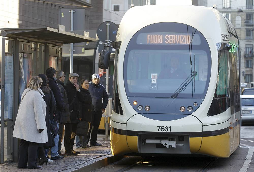 Photo: People wait at a stop as a tram passes by in Milan, Italy