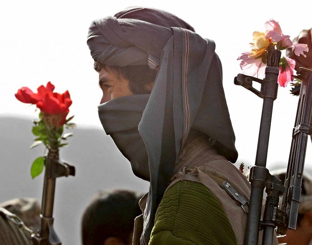 Photo: A Northern Alliace fighter walks with flowers in his Kalashnikov mashine gun, at the front line near the town of Khanabad, northern Afganistan, 2001