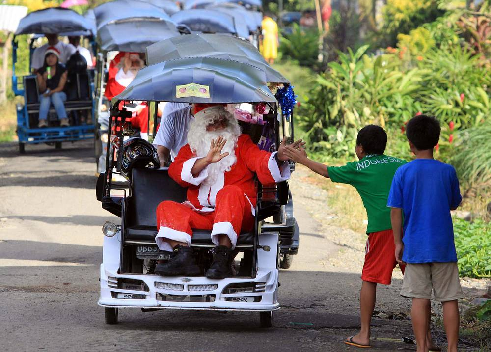 Photo: Indonesian Santa Claus on a three-wheeled motorized pedicab greets children during a Christmas parade in Bolaang Mongondow, Indonesia