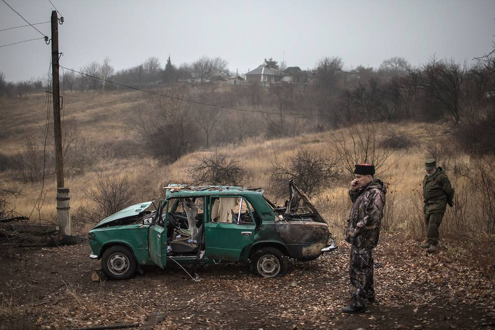 As of UN report from 14 November, estimated number of  people living in conflict-affected areas is 5.2 million. Photo: Local militia men stand near destroyed Lada car, Luhansk region
