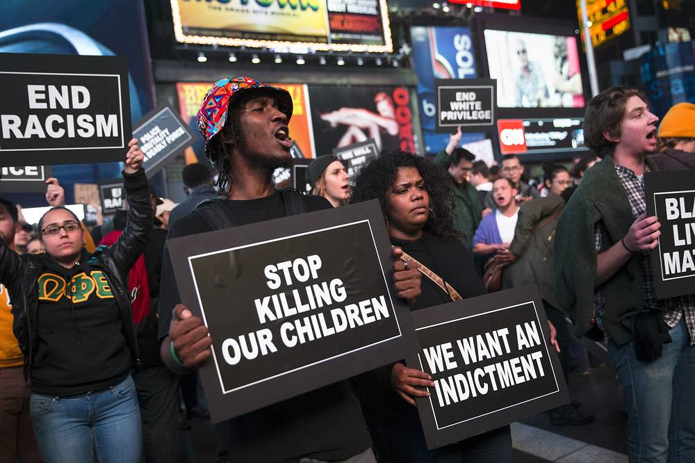 Photo: Protestors hold signs during a demonstration in Times Square, New York, US