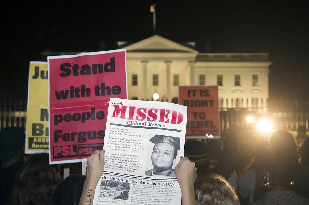 US President Barack Obama called for calm in the wake of the grand jury's announcement. Photo: People hold placards outside the White House while protesting against the grand jury decision not to indict Ferguson police officer Darren Wilson in the 09 August shooting death of Michael Brown