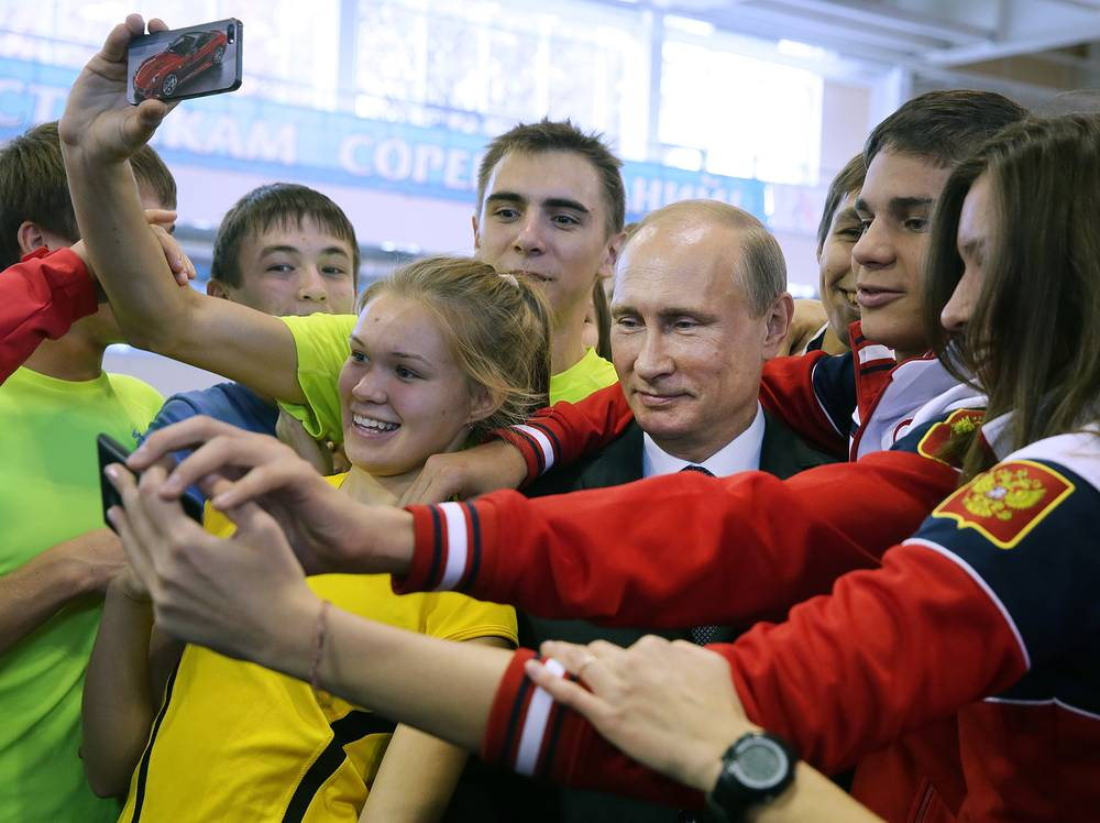 Winners of the Nanjing 2014 Summer Youth Games takea selfie with Russian President Vladimir Putin (center)