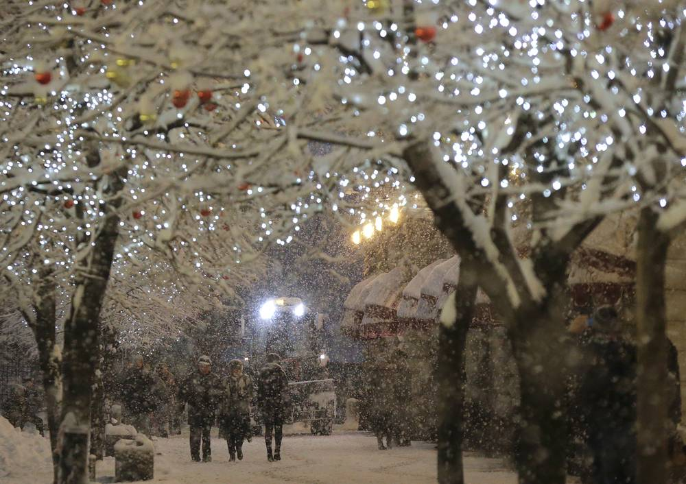 Photo: Snow covered trees decorated with Christmas lights in central Moscow