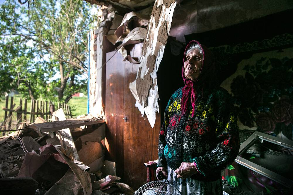 Woman stands among the ruins of her house in the Donetsk Region destroyed by Ukraine's artillery strikes