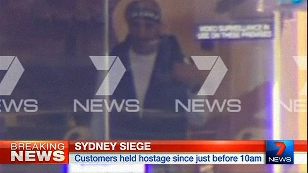 Police have established contact with the armed hostage taker. Photo: A man believed to be a gunman inside a cafe in Sydney