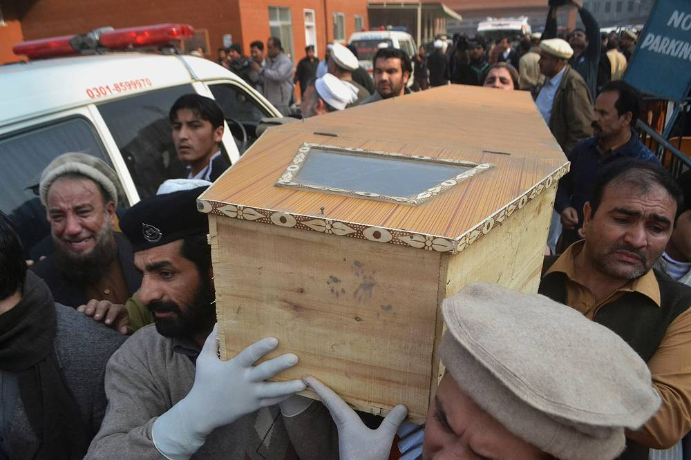 Photo: People carry the casket of a victim of Taliban attack in a school in Peshawar