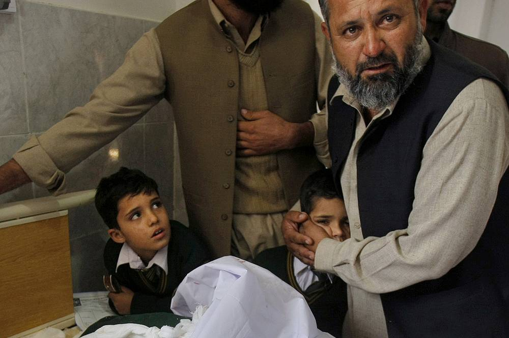 The terrorists are reported to have suicide belts, grenades and automatic rifles. Photo: A Pakistani man with students at the bedside of a boy injured in a Taliban attack on a school in Peshawar