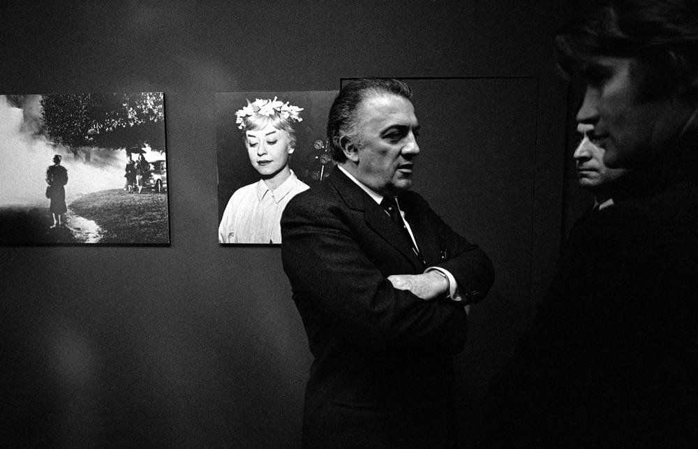 "Federico Fellini in front of a portrait of his wife, Italian actress Giulietta Masina, 1970 at the opening of an exhibition of still photographs from his film ""Le Notti di Cabiria"" (Nights of Cabiria) in Germany.  Fellini won his second Academy Award for this film in 1957"