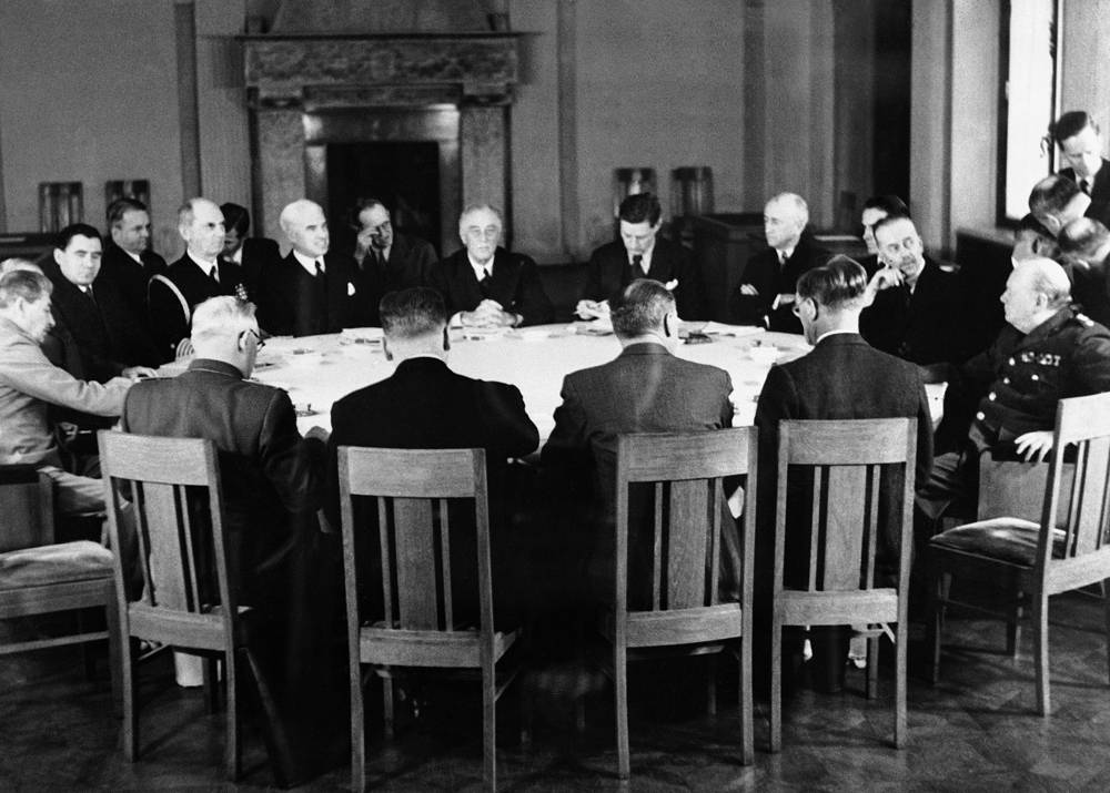 The Big Three conference in progress with those seated round the table (left to right) are: Soviet Marshal Joseph Stalin, Andrei Gromyko, US Admiral William Leahy, US Foreign Secretary Edward Stettinius, US President Franklin Roosevelt,  US Ambassador to the Soviet Union, Averell Harriman, Sir Alexander Cadogan (Permanent Under Secretary to the Foreign Office), Director of War Mobilization and Recoversion James F. Byrnes and British Prime Minister Winston Churchill, February 12, 1945
