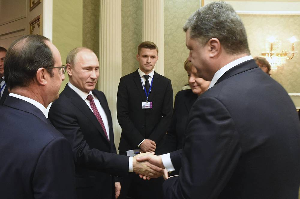 Russian President Vladimir Putin and Ukrainian President Petro Poroshenko shaking hands as French President Francois Hollande and German Chancellor Angela Merkel looking on during a meeting in Minsk, Belarus