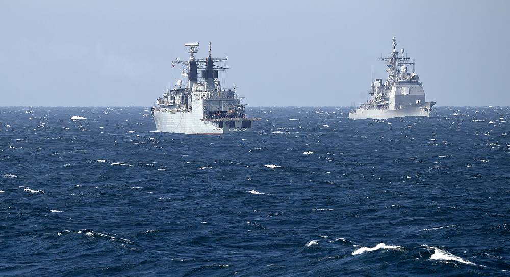 Romanian navy frigate Regina Maria (left) crosses with USS Vicksburg