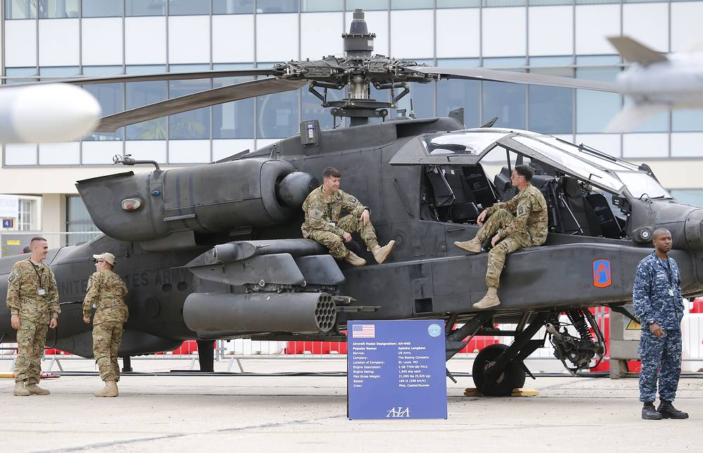 US army personnel standing on the Boeing Helicopter AH-64D Apache Longbow