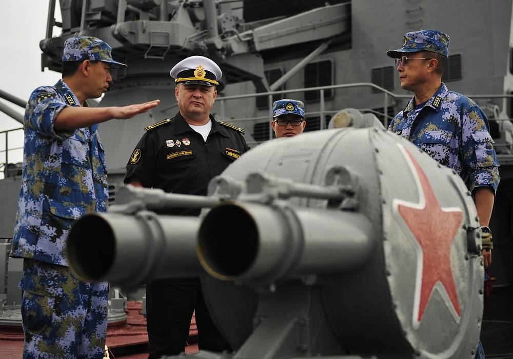 Russian cruiser Varyag deputy captain Sergei Vertepa showing Chinese navy officers around the cruiser during the joint Russian-Chinese military exercises