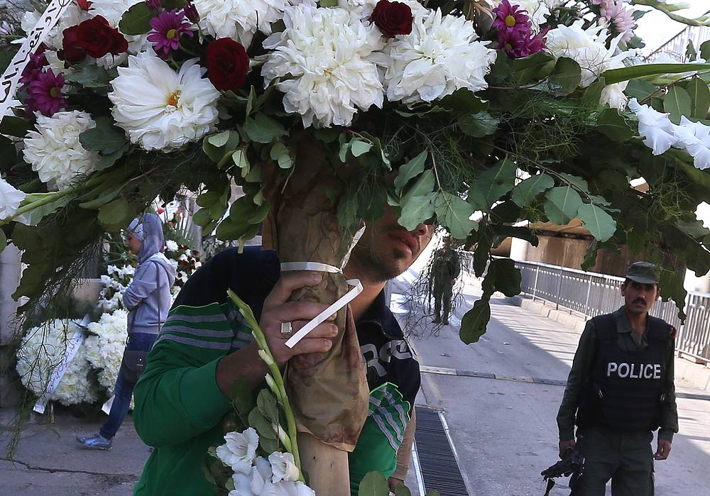 A man with flowers outside the Russian Embassy in Damascus, Syria