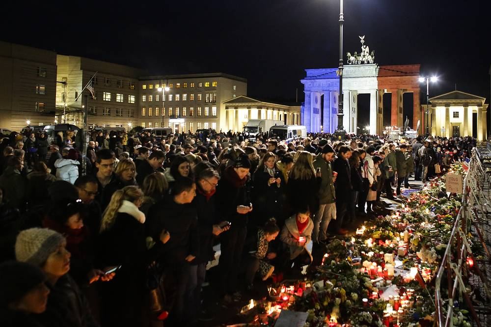 Brandenburg Gate, illuminated in the French national colors, and people laying down flowers in front of the French Embassy in Berlin, Germany