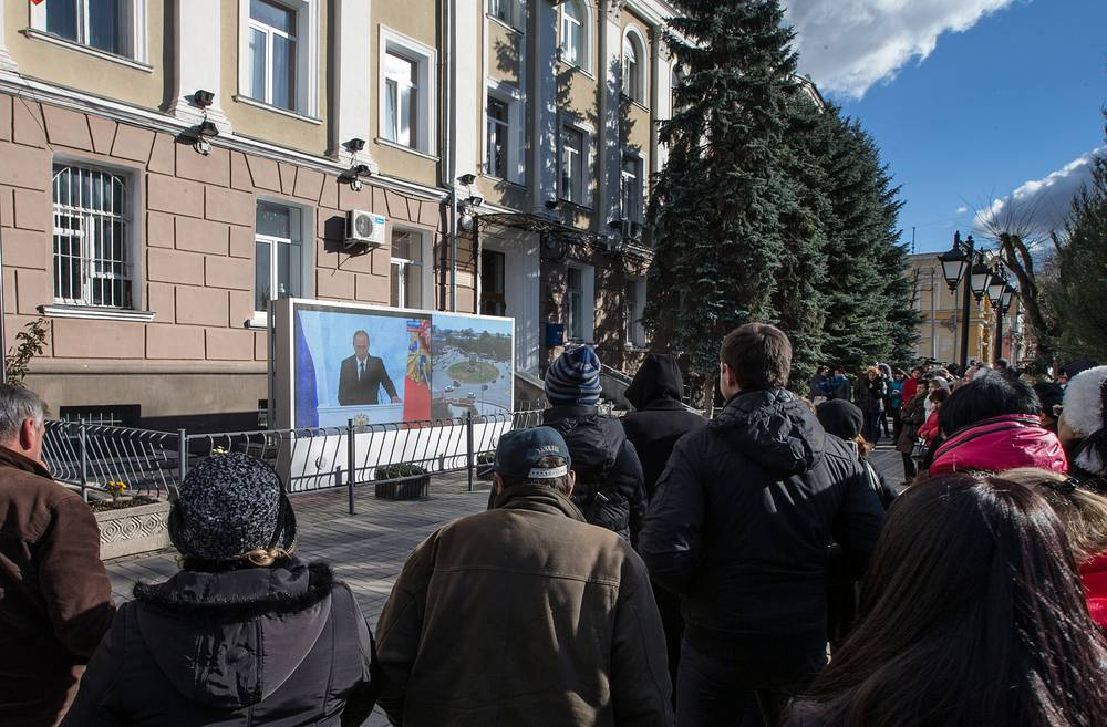 Crimean residents watch the president's address