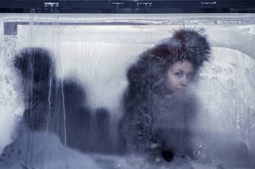 A woman looking out of a bus window covered with frost in Novosibirsk, January 25, 2015