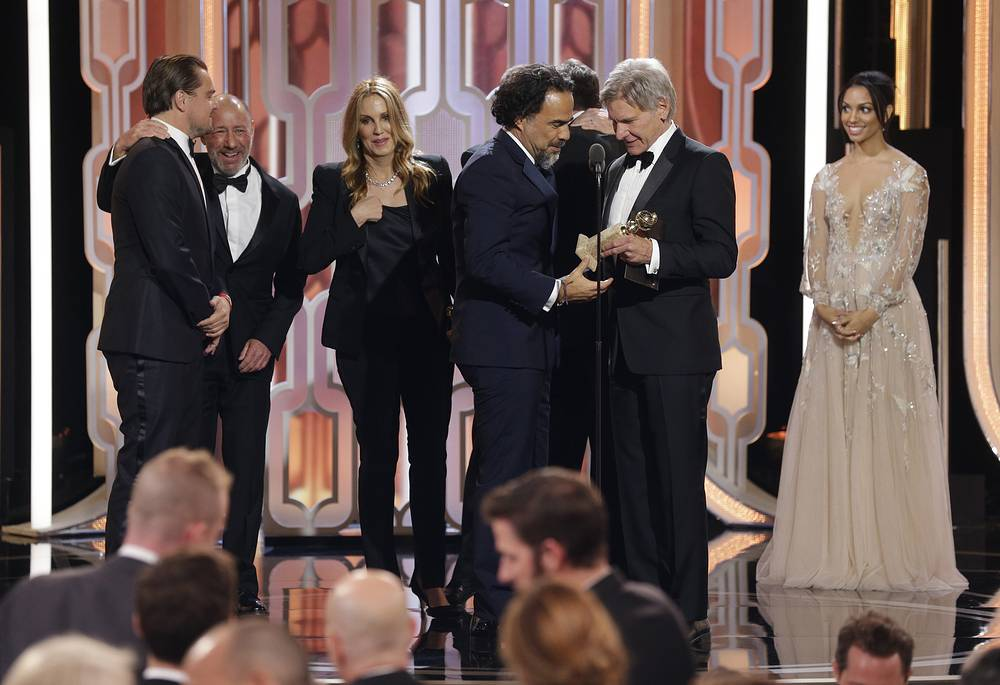 """Director Alejandro G. Inarritu accepting the award for best motion picture drama for """"The Revenant"""", from presenter Harrison Ford"""