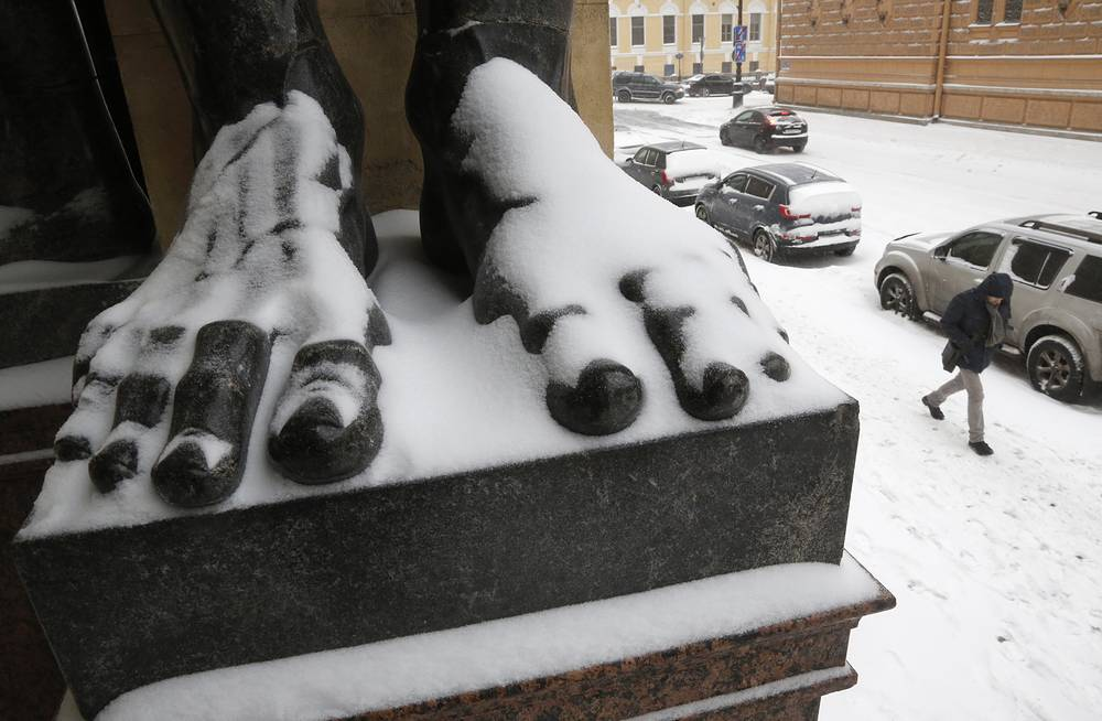 Snow covers foots of a sculpture of Atlas at the State Hermitage museum after snowfall in St.Petersburg