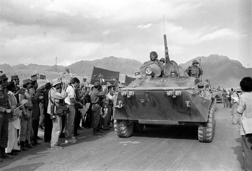 Afghans greeting the first column of armoured personnel vehicles riding from Jalalabad in Kabul as Soviet troops returning home from Afghanistan