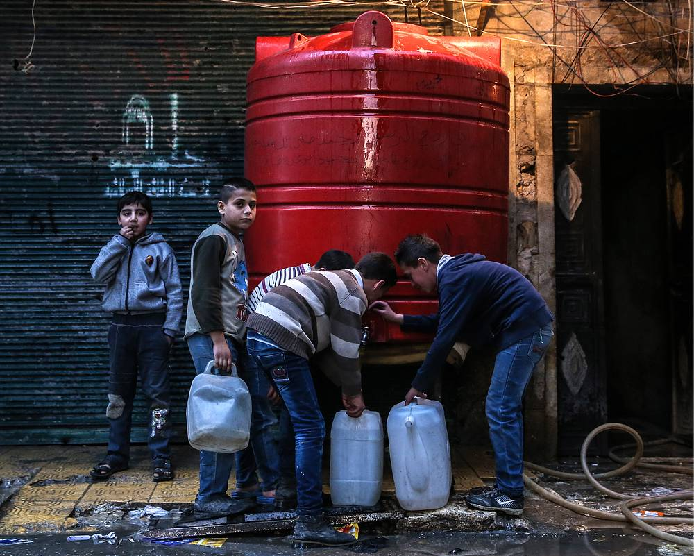 Boys fill containers with drinking water from a tank in Aleppo
