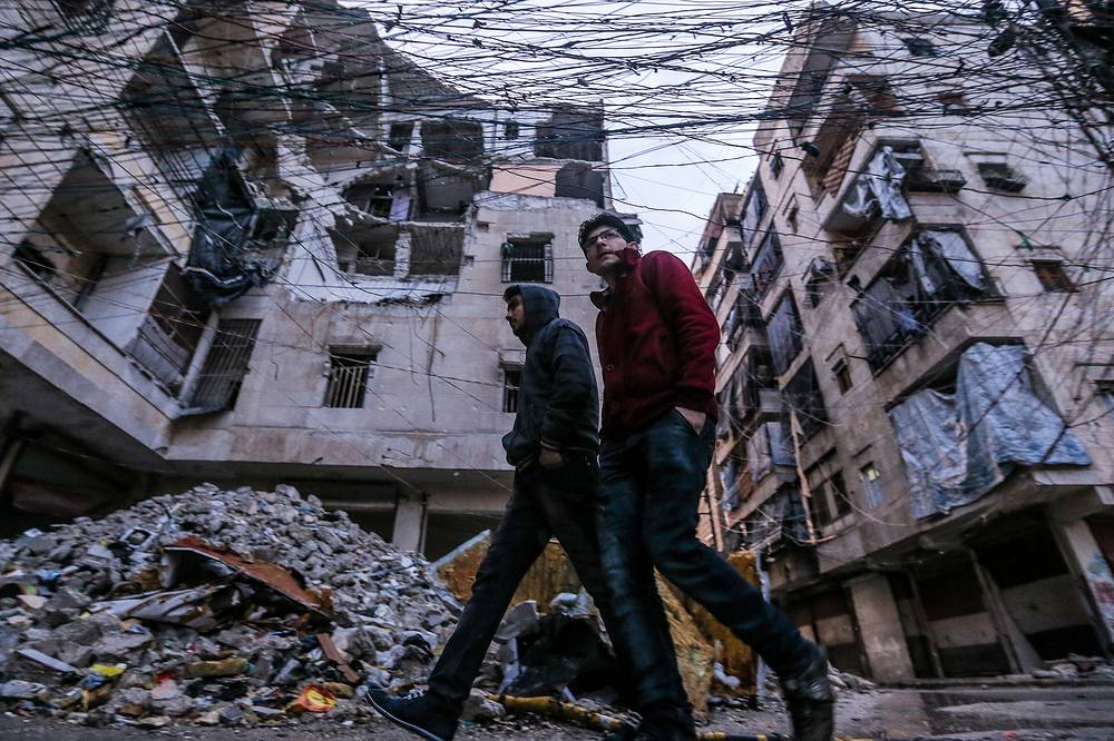 People walking past piles of rubble and partially destroyed buildings in Salah al-Din, Aleppo