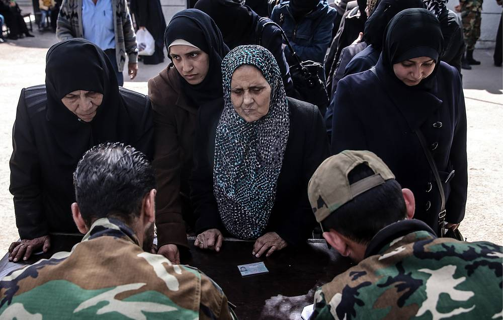 Civilians at a check point they have to cross to enter the Qadam neighborhood of Damascus
