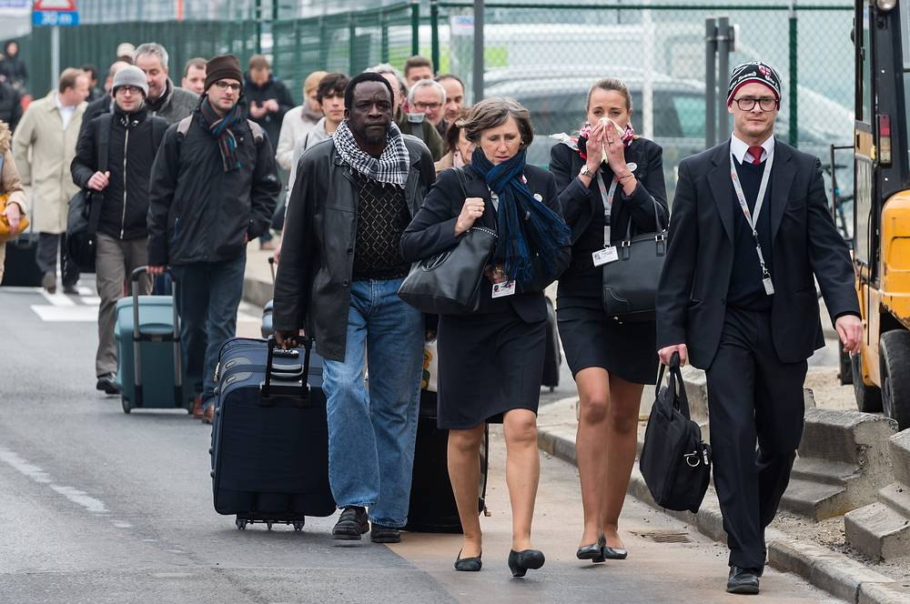 People walking away from Brussels airport after explosions rocked the facility