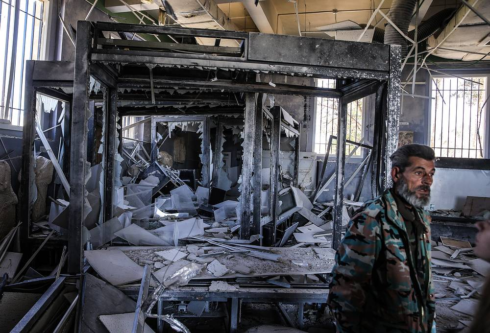 A Syrian government army soldier next to a display of ancient artifacts vandalised by IS militants in the National Museum of Palmyra