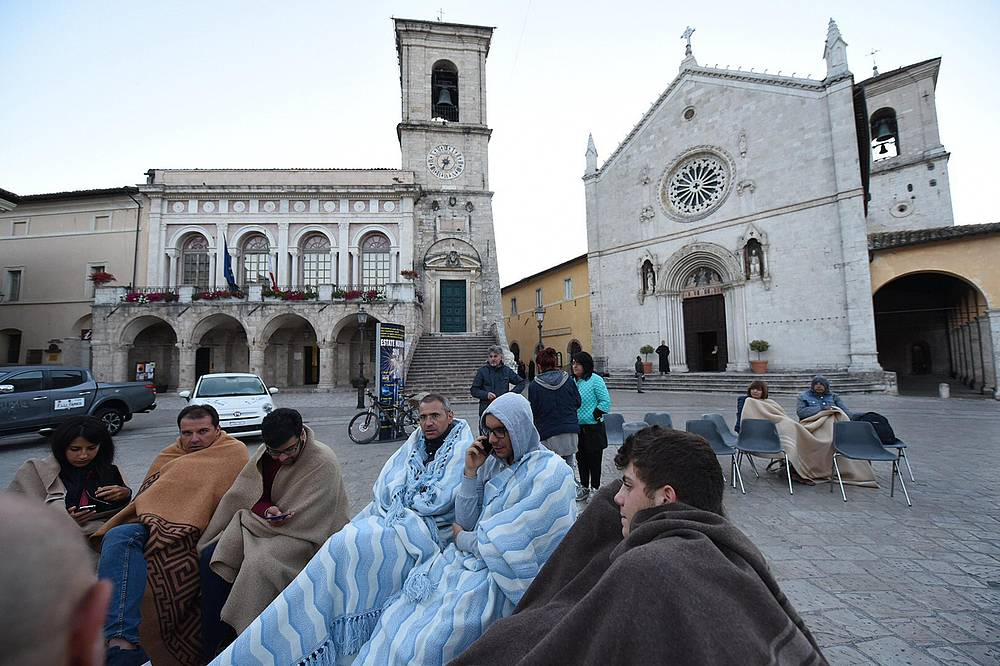 People outside after spending the night on a street after an earthquake hit central Italy in Norcia