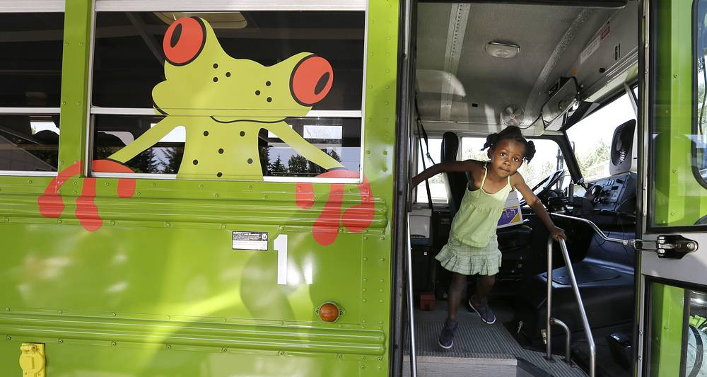 A child exits a school bus cruising in low-income neighborhoods in Seattle, USA